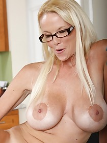 Blond-haired MILF bombshell takes off her black panties in the kitchen