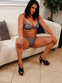 Tanned and thick brunette with tats masturbating on a white couch