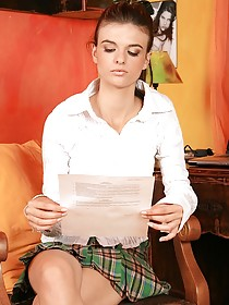 Skirt-wearing teen undressing and touching herself in a chair