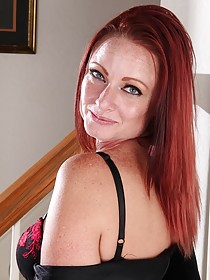 Redheaded mature lady showing her sexy body next to the stairs